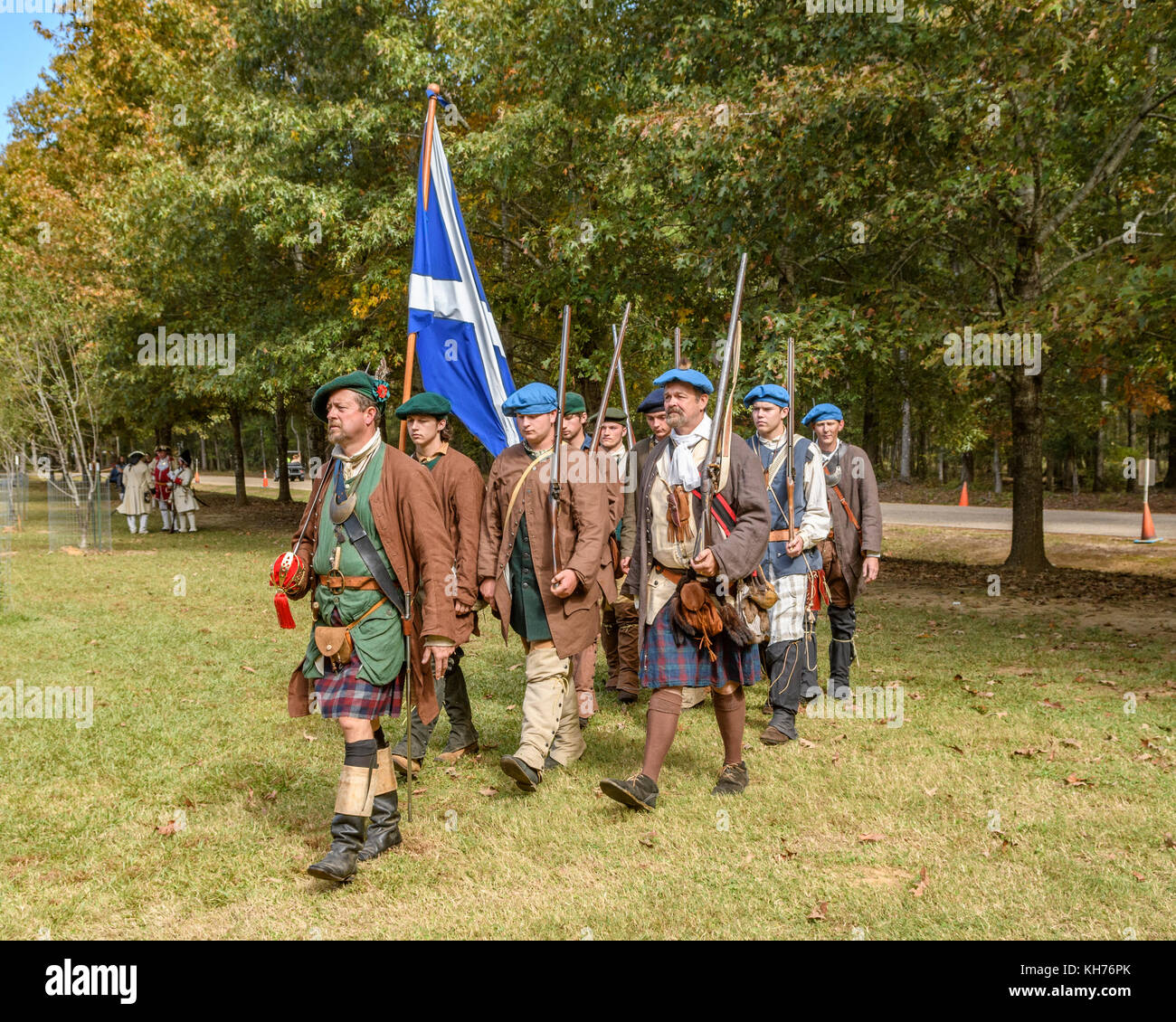 Reenactment actors dressed as Scottish army soldiers of the early 1700's marching with the flag of Scotland. - Stock Image