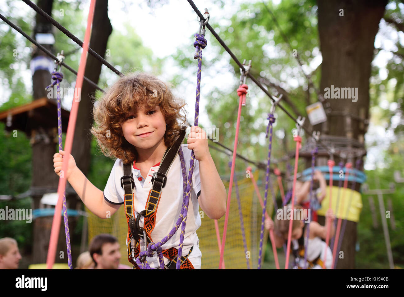 cute curly child in a rope park - Stock Image