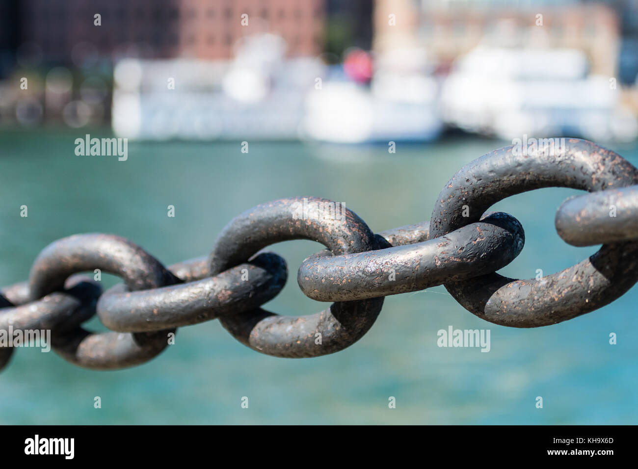 Five Links in Iron Chain hanging in front of water - Stock Image