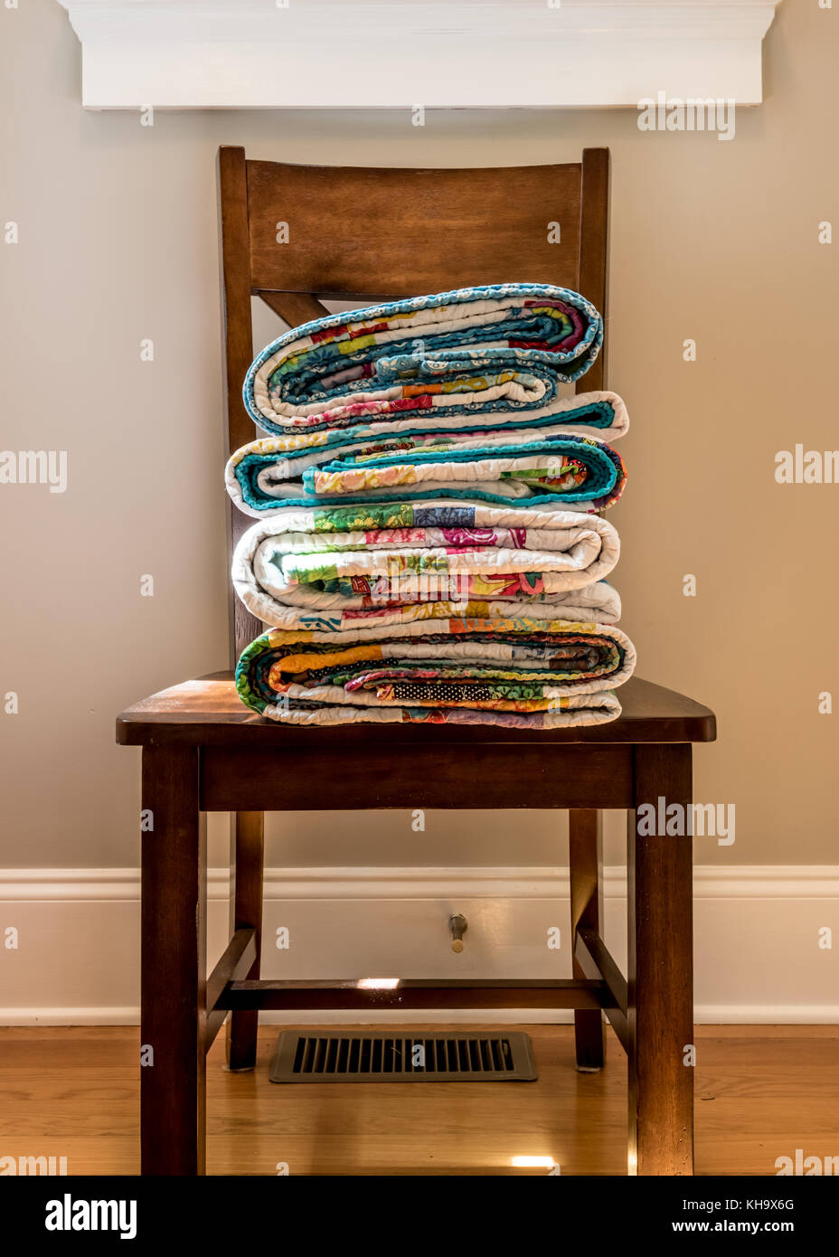 Folded End of Quilts on Kitchen Chair in sunlight - Stock Image