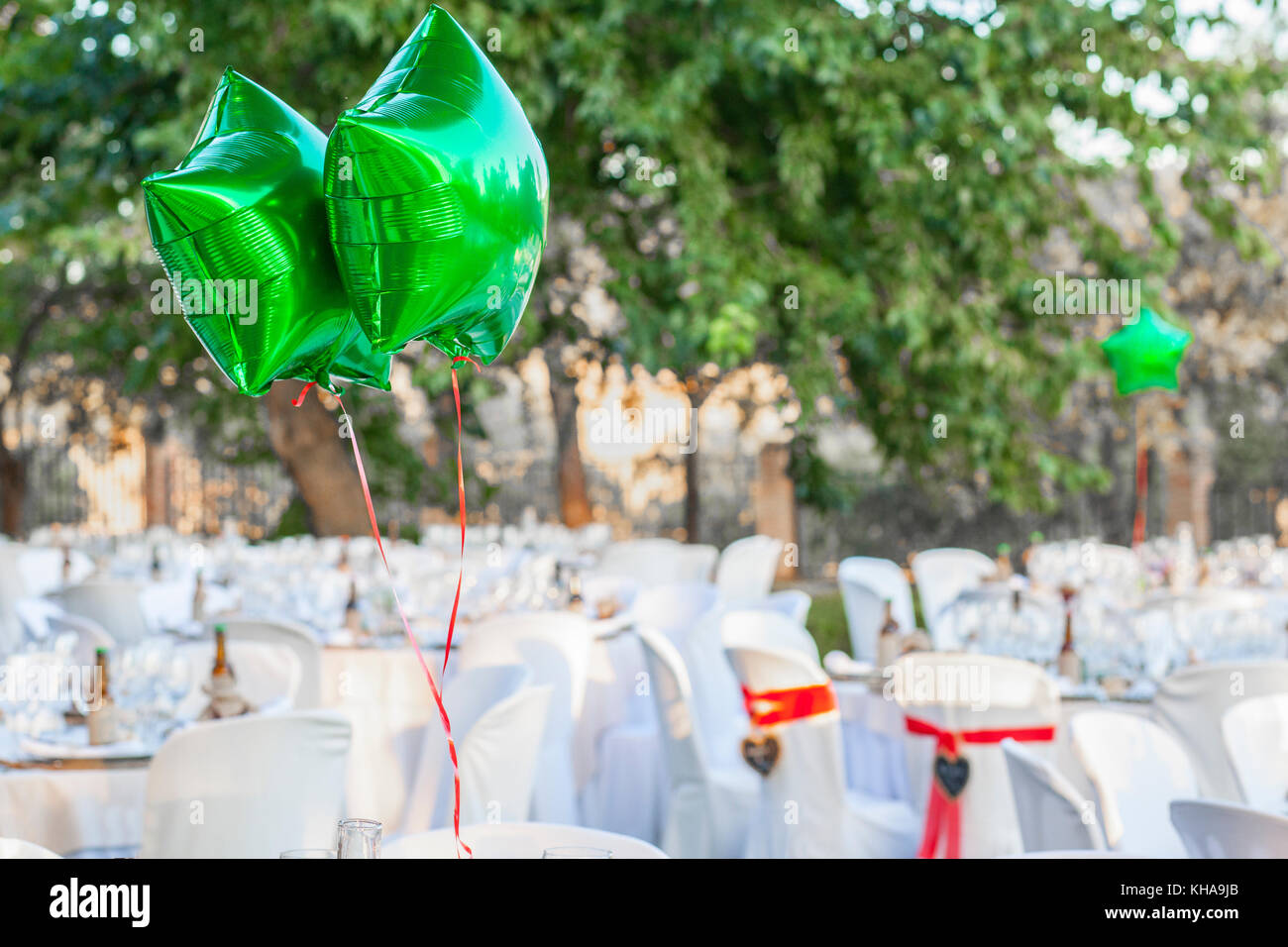 Green Shiny Balloons At Garden Table Setting For Wedding Reception