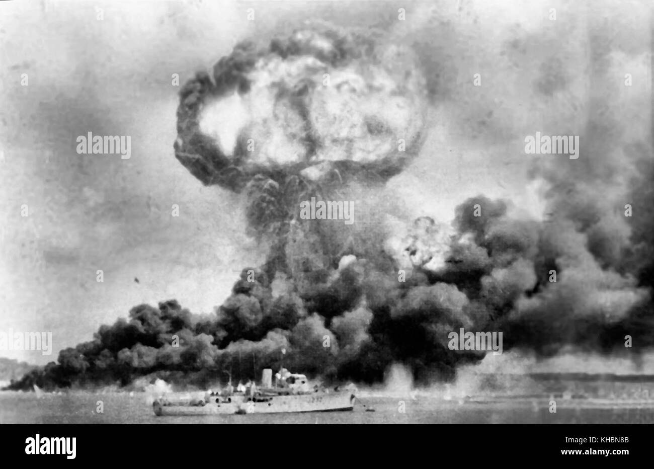 The explosion of the MV Neptuna and clouds of smoke from oil storage tanks, hit during the first Japanese air raid - Stock Image