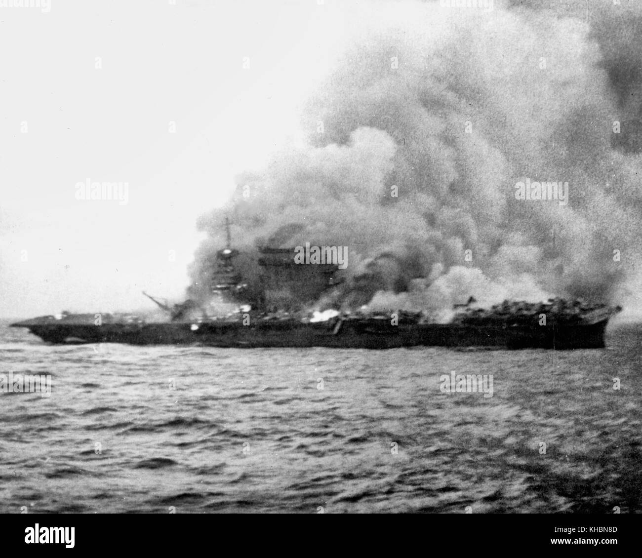 The U.S. Navy aircraft carrier USS Lexington (CV-2), burning and sinking after her crew abandoned ship during the - Stock Image