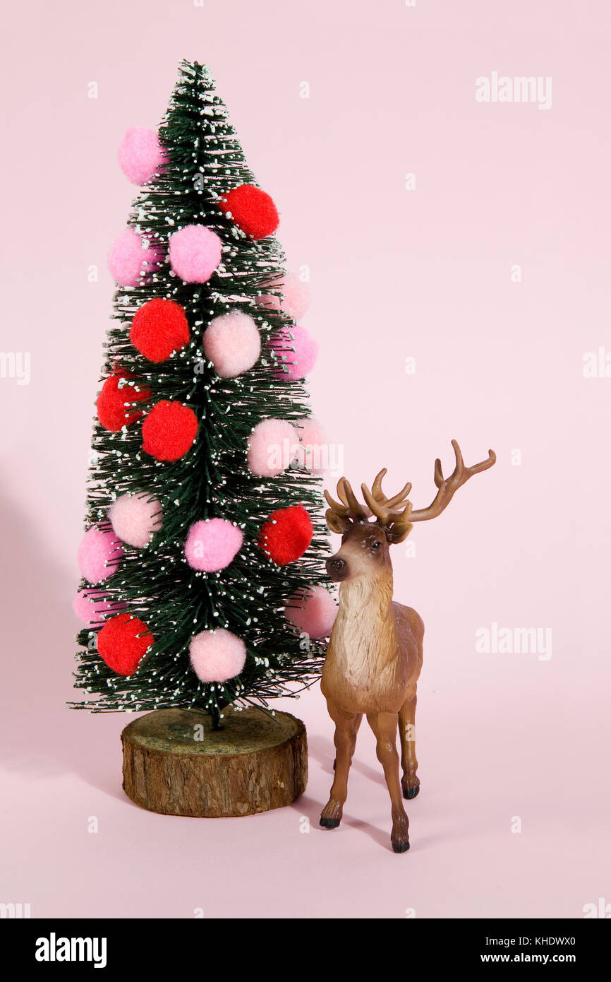 snowy decorated firs and decorated christmas tree with pompom with figurine reindeer next to it on a vibrant pink - Stock Image
