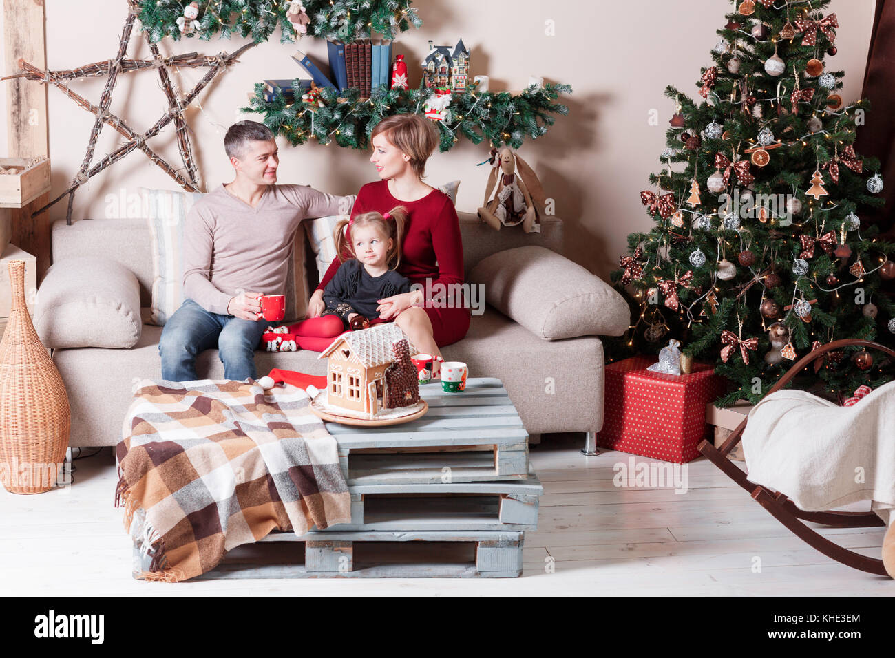 Portrait of young friendly family on Christmas morning. Father, mother and daughter - Stock Image