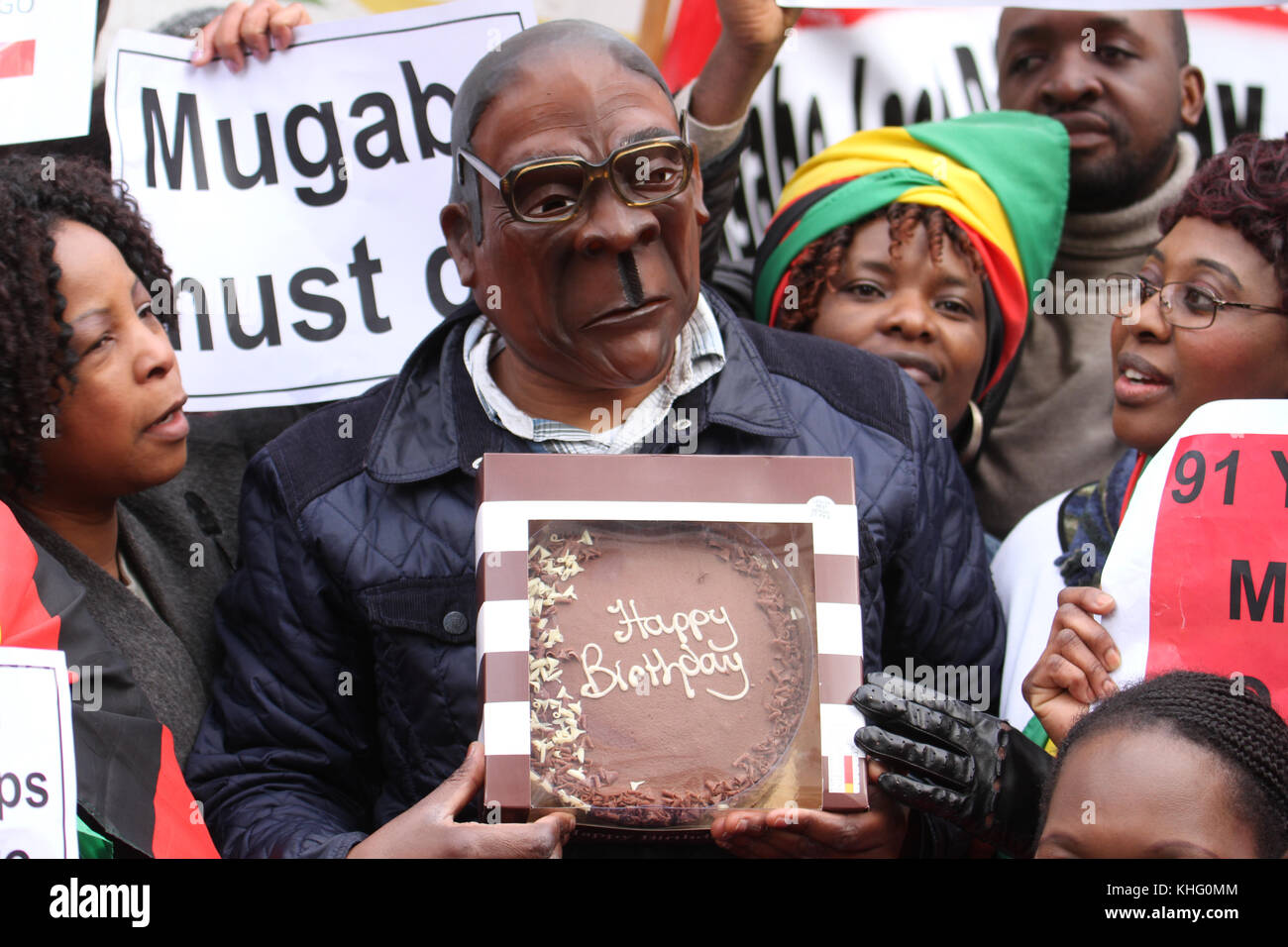 London, UK. 21 February 2015: A mand with a Mugabe mask hold a birthday cake outside Zimbabwe House in central London - Stock Image
