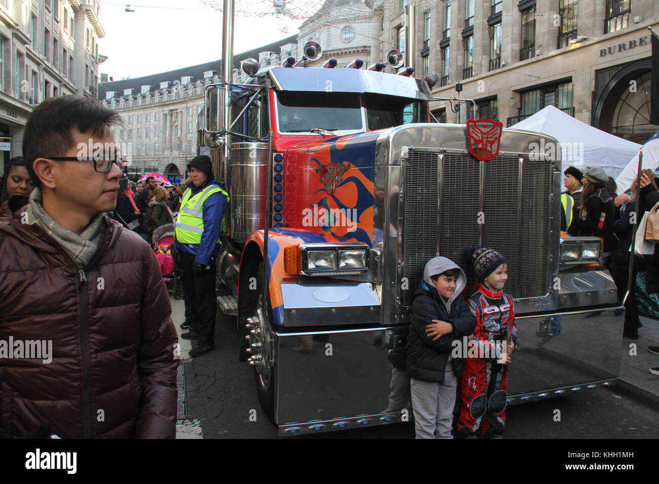 London, UK. 19th Nov 2017.  Two children pose by a Transformer truck at Hamleys Christmas Toy Parade on a traffic - Stock Image