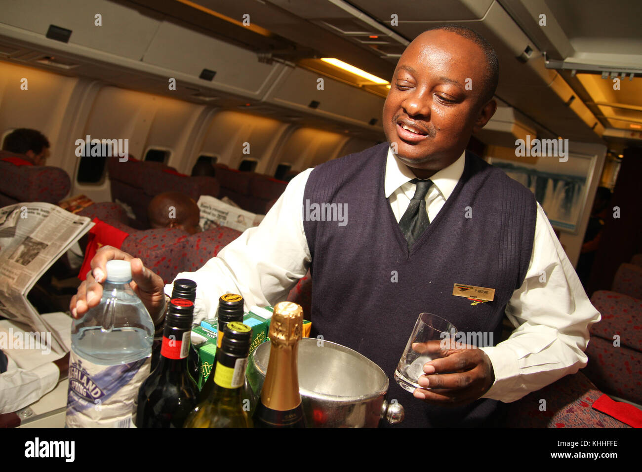 GAtwick, UK - 10 October 2011: A flight attendant ready to serve drinks on the London to Harare flight. Credit: - Stock Image
