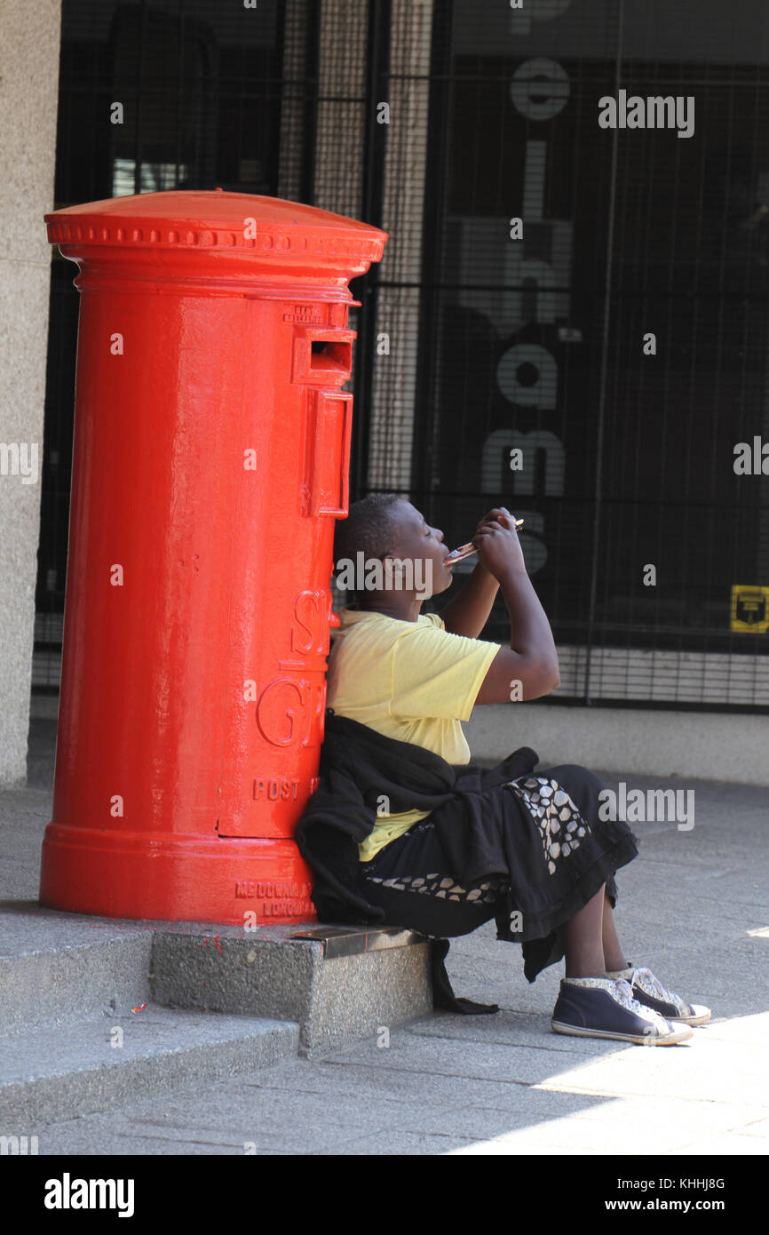 BULAWAYO, ZIMBABWE - 15 October 2011. A woman enjoys her lunch sat by a red mailbox with the initials SR GPO (Southern - Stock Image