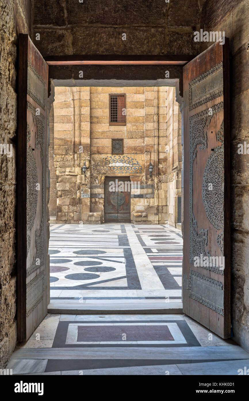 Opened door leading to the courtyard of Al-Sultan Al-Zahir Barquq mosque. Al-Moez Street, Old Cairo, Egypt - Stock Image