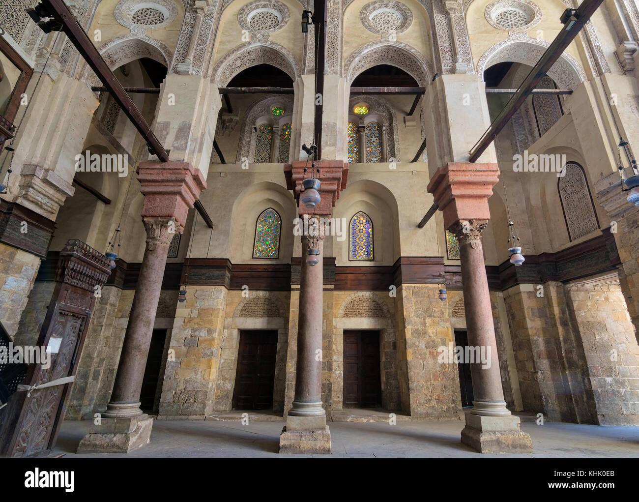 Interior of Sultan Qalawun Mosque with stone columns, colored stained glass windows and wooden doors, Cairo, Egypt - Stock Image