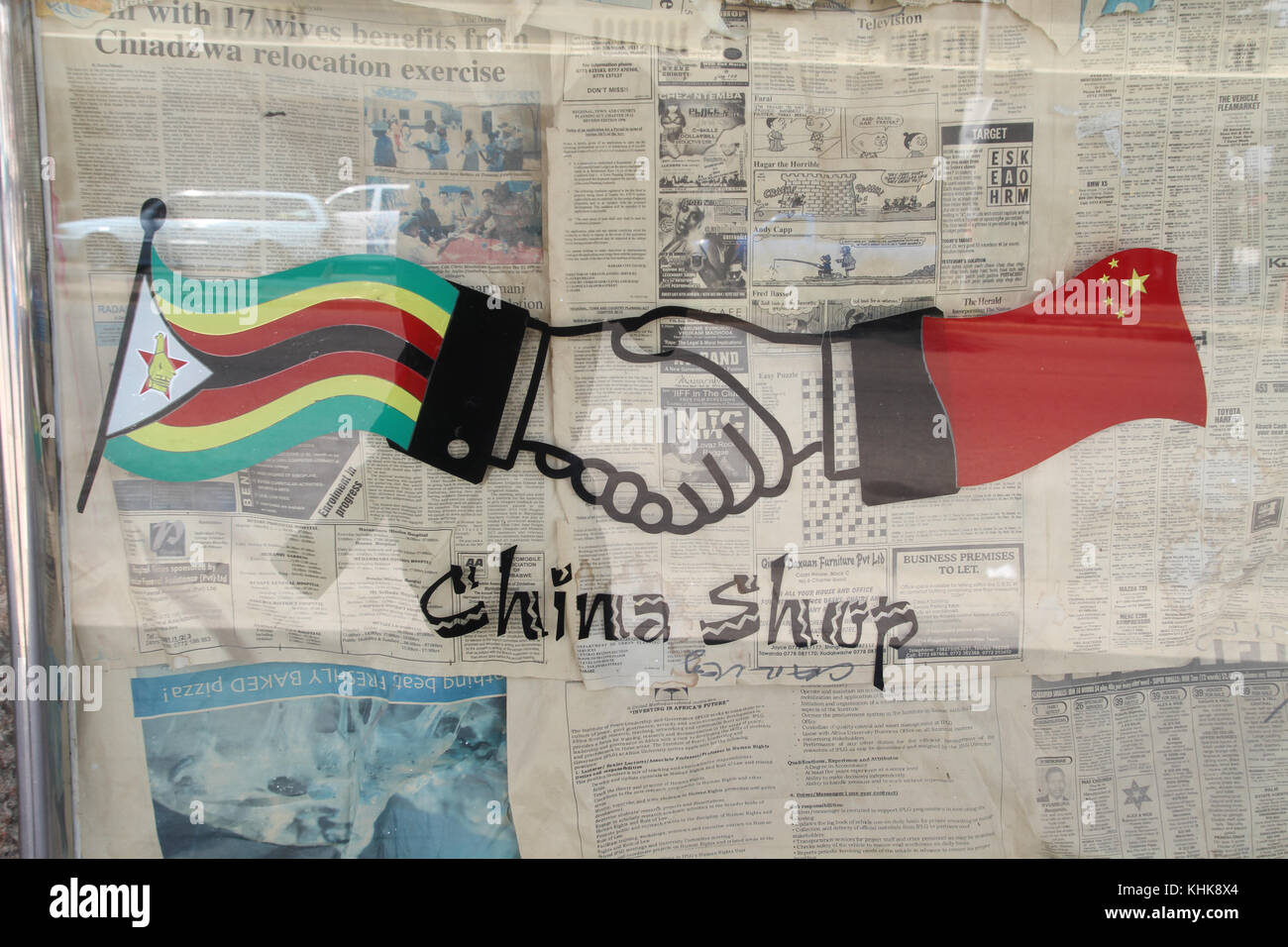 Mutare, ZIMBABWE -  15 October 2011. A sign showing a handshake between the  Chinese and Zimbabwe at a shop window - Stock Image