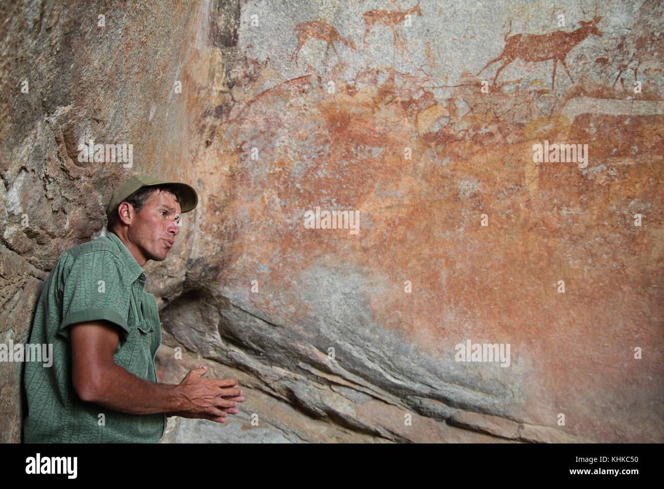 MATOPO, ZIMBABWE -  17 October. Game ranger Ian Harmer talks to tourists about bushmen rock painting in the Nswatugi - Stock Image