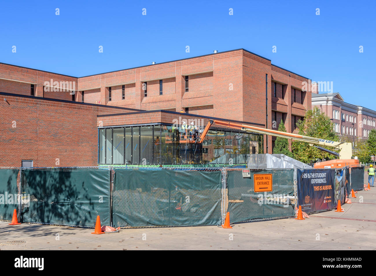 Two men construction workers on a JLG telescopic boom lift working on a building expansion at Auburn University, - Stock Image