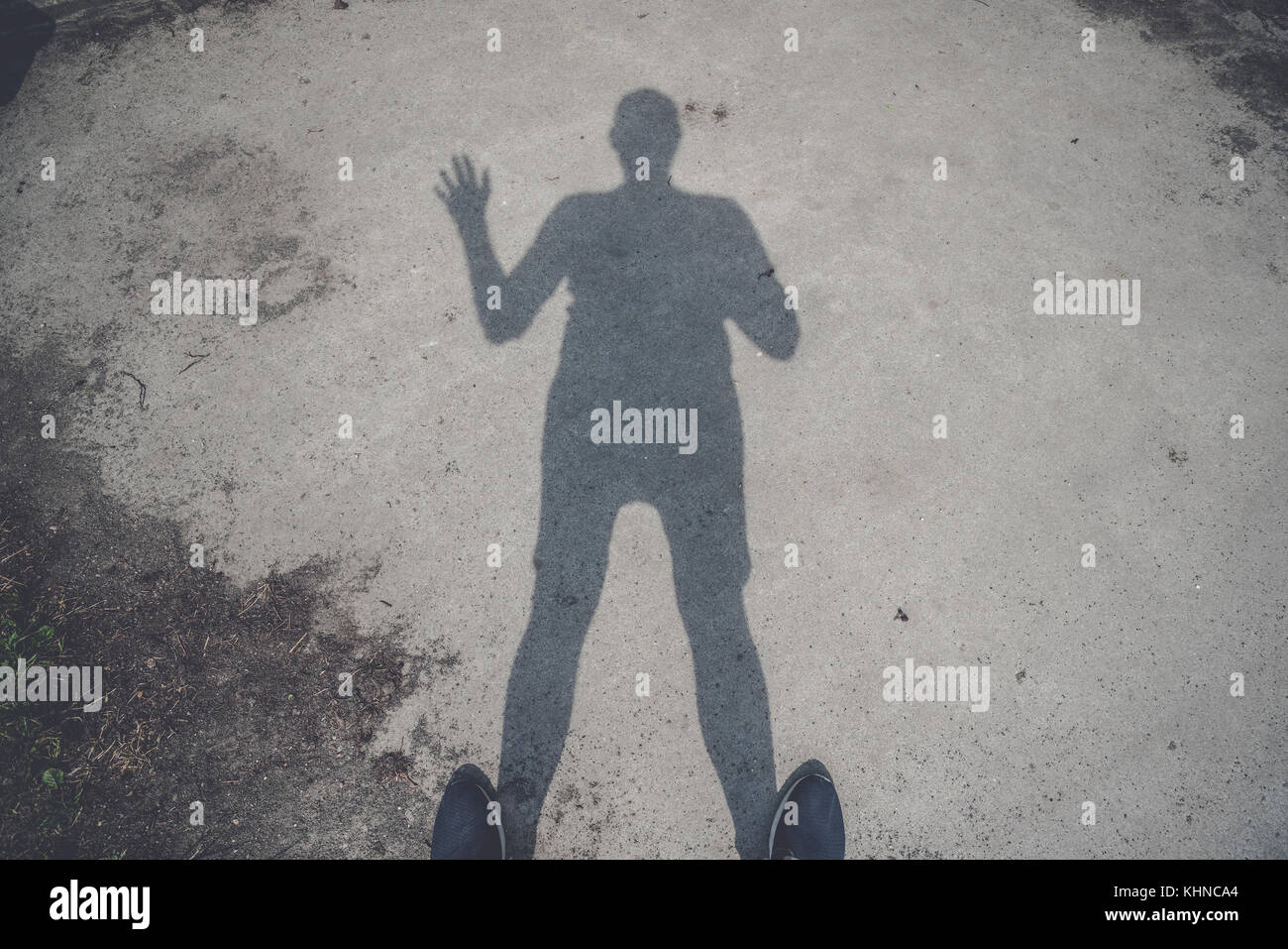 Male shadow on the ground waving hello with one hand - Stock Image