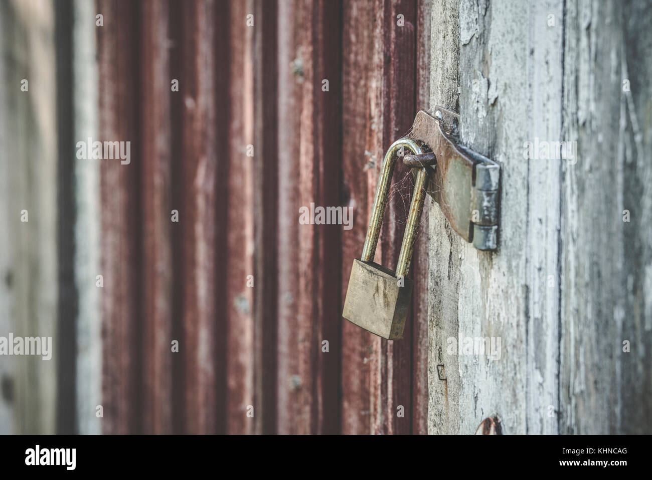 Old lock on a wooden door in golden color in a weathered grunge look - Stock Image