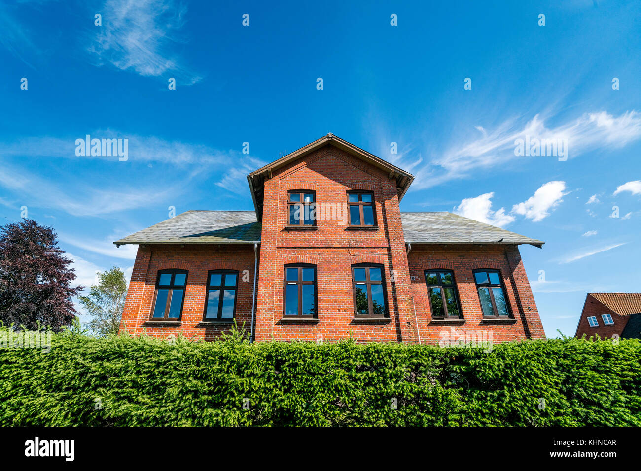 Large brick house in red color behind a green hedge in the summer with blue sky - Stock Image