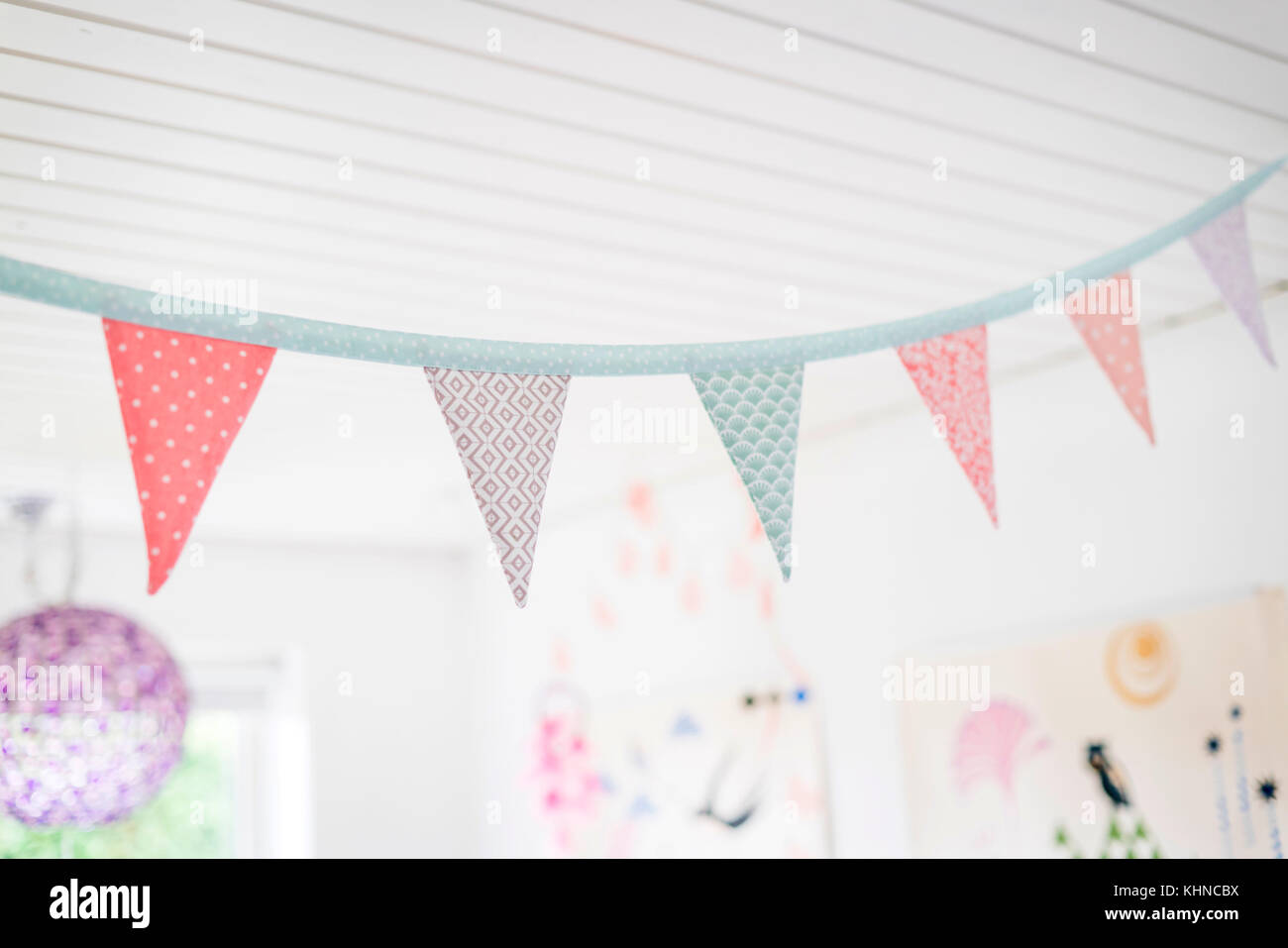 Colorful birthday flags in kids playroom in bright light - Stock Image