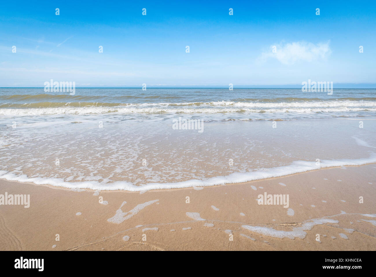 Waves coming in on a Scandinavian beach in the summer under a blue sky with a white cloud - Stock Image