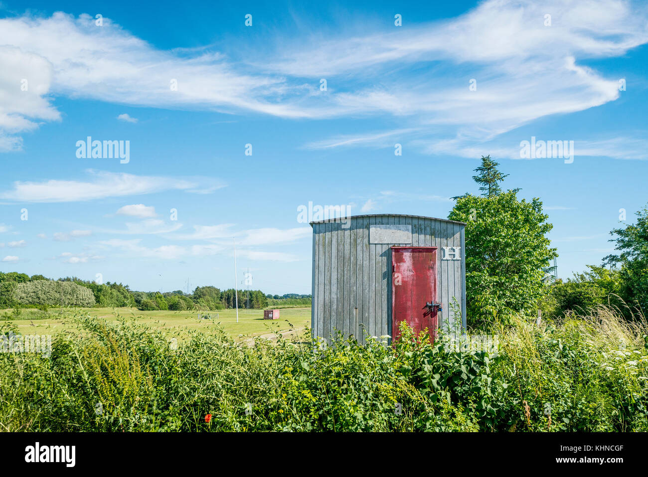 Wooden shed on a rural field in a countryside with green fields and plants - Stock Image