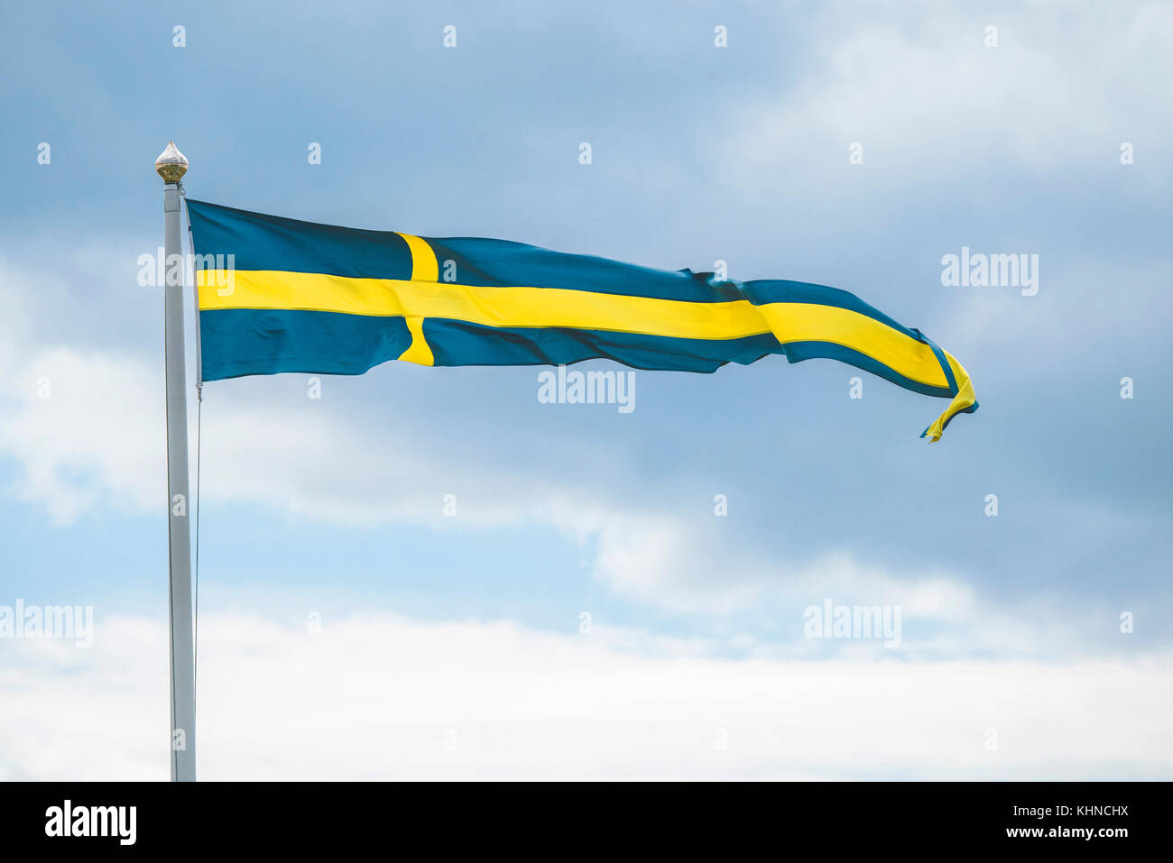 Swedish pennant flag on a flagpole in the wind in blue and yellow colors in cloudy weather - Stock Image