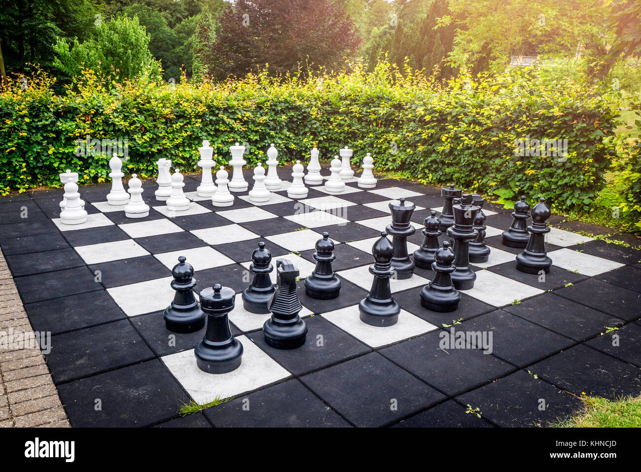 Large outdoor chess game on a garden terrace in a yard with a green hedge and sunshine - Stock Image