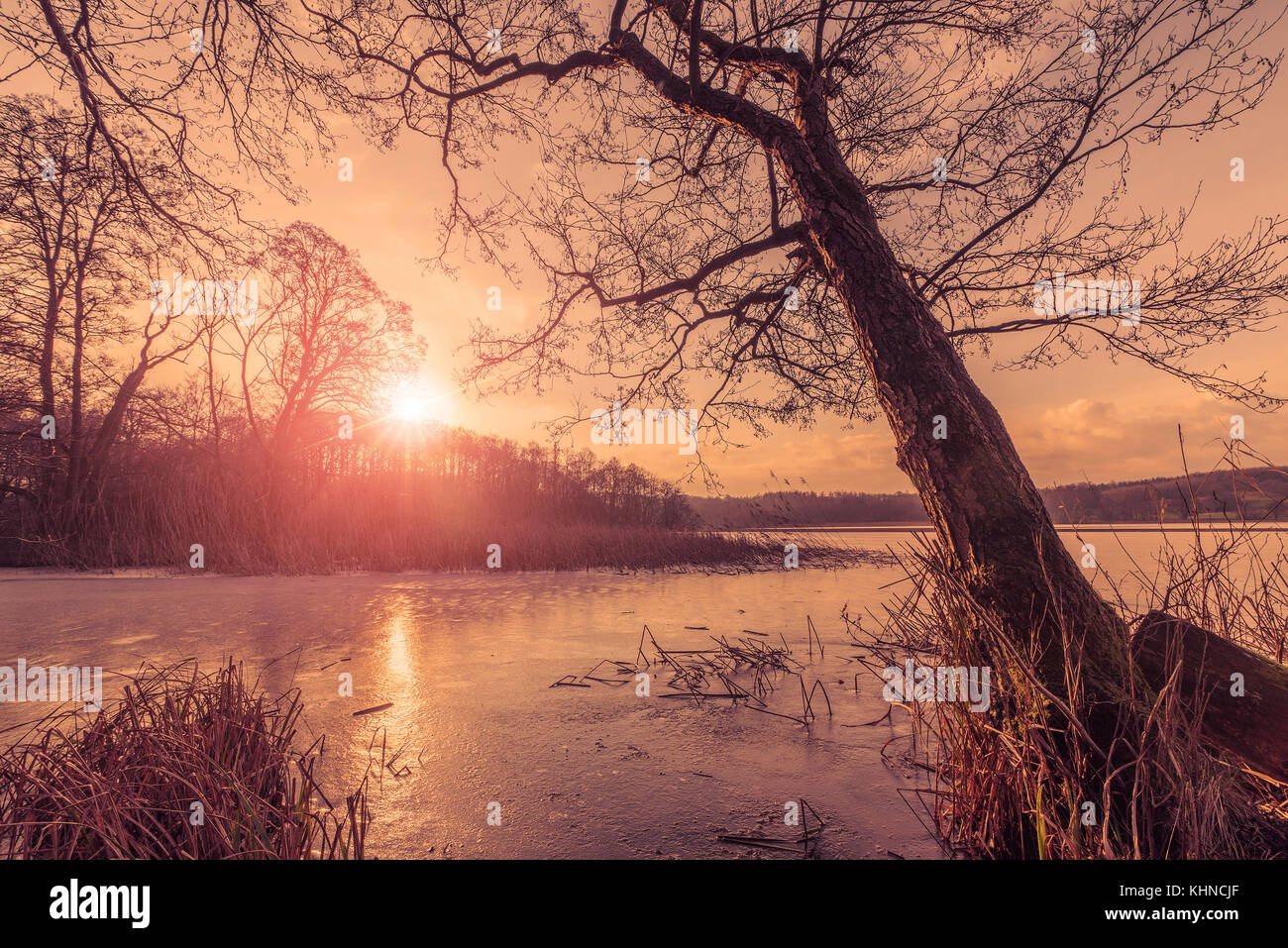 Sunset over a frozen lake in the winter with reflections of the sun on the cold ice - Stock Image