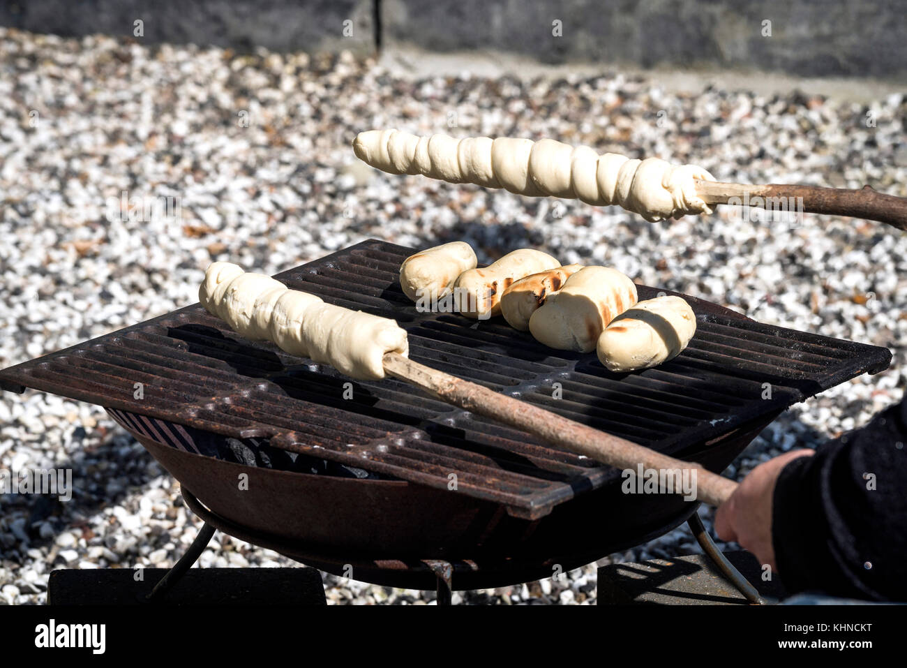 Bread on an outdoor grill with raw dough on a stick ready to be baked - Stock Image