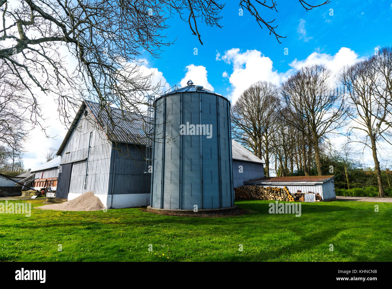 Small farm with a large silo in a rural environment in the springtime - Stock Image