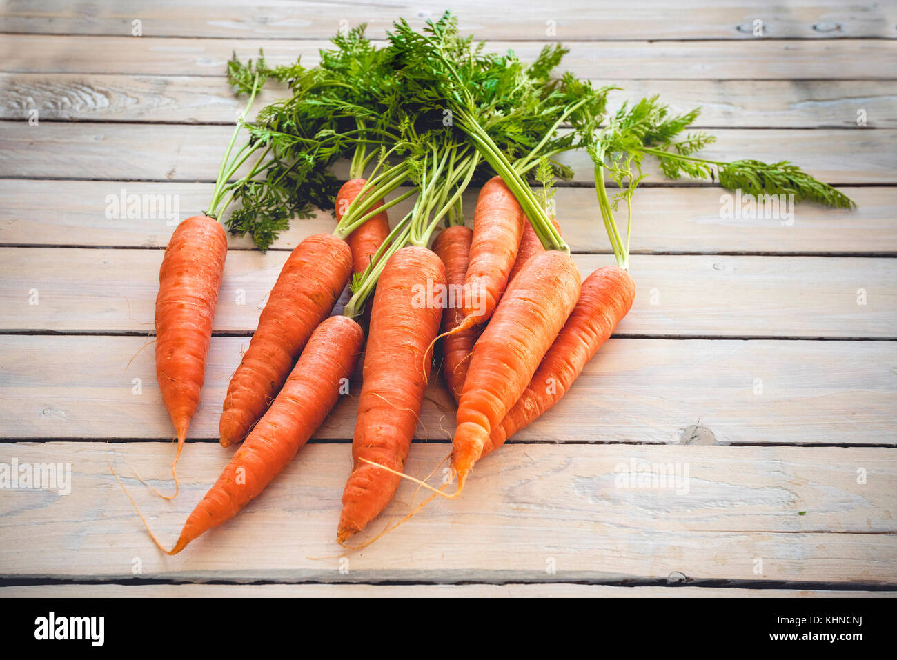 Raw carrots with green plants on a wooden table - Stock Image