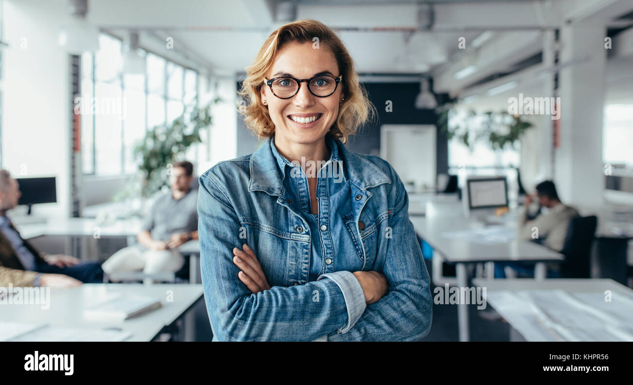 Happy female executive standing with arms crossed. Young  businesswoman standing in office. - Stock Image