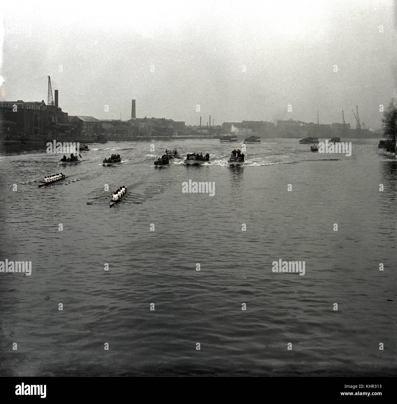 1950s, historial picture showing the boats and flotilla of the famous university rowing race, the Oxford & Cambridge - Stock Image