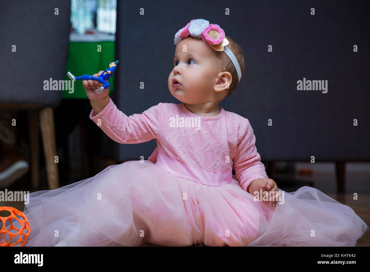 Brunette baby girl in pink dress sitting on the floor looking to the right - Stock Image