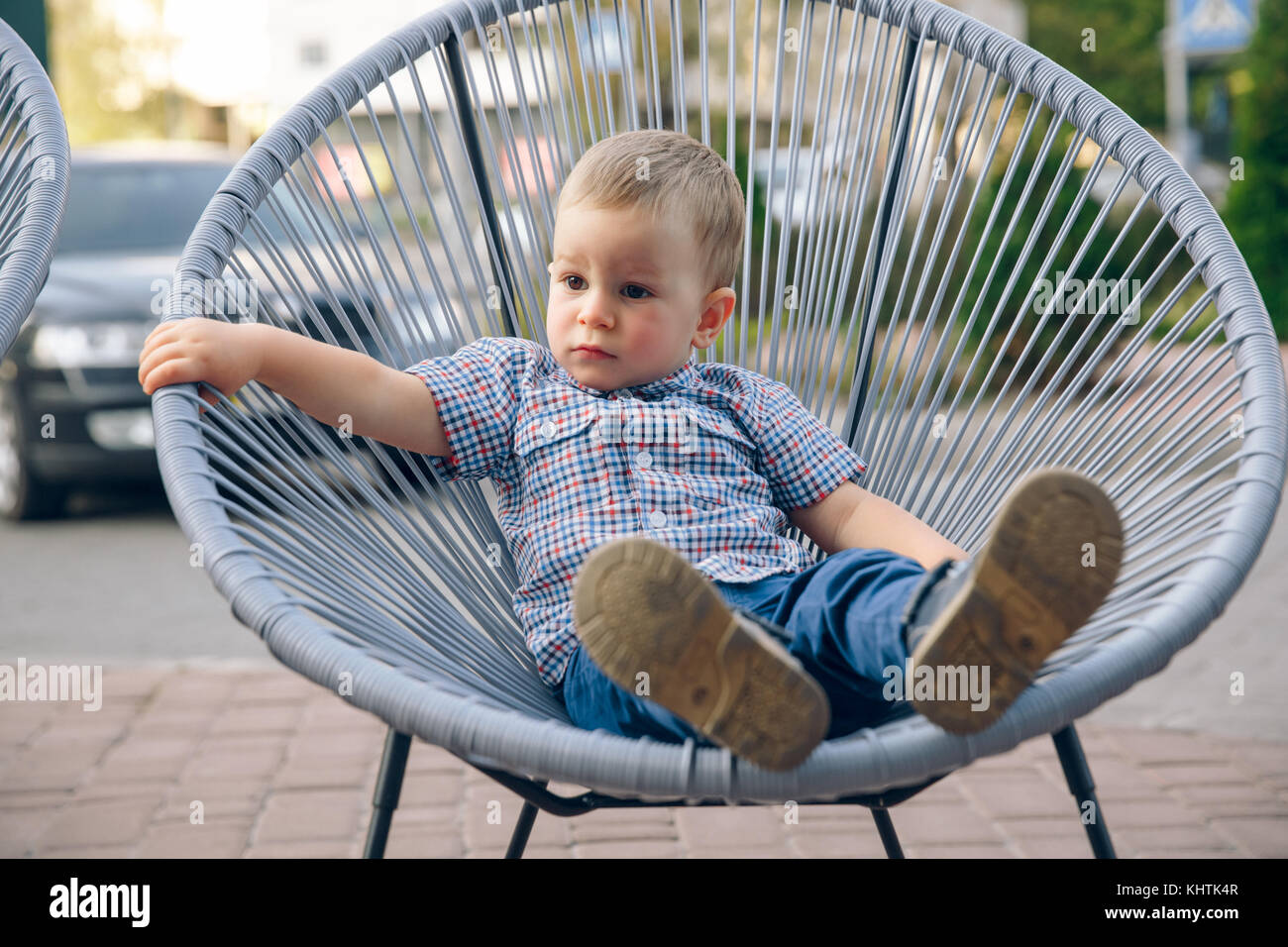 Ginger toddler dressed in jeans and blue t-shirt sitting on open air in wicker chair. - Stock Image