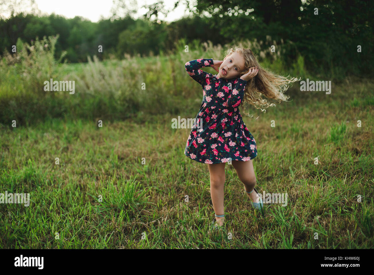 Blond haired girl running and pulling a face in field - Stock Image