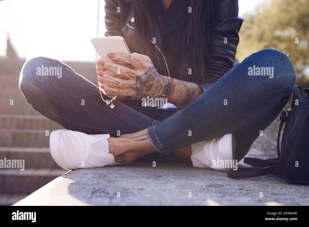 Young woman sitting on wall, using smartphone, tattoos on hand, low section - Stock Image