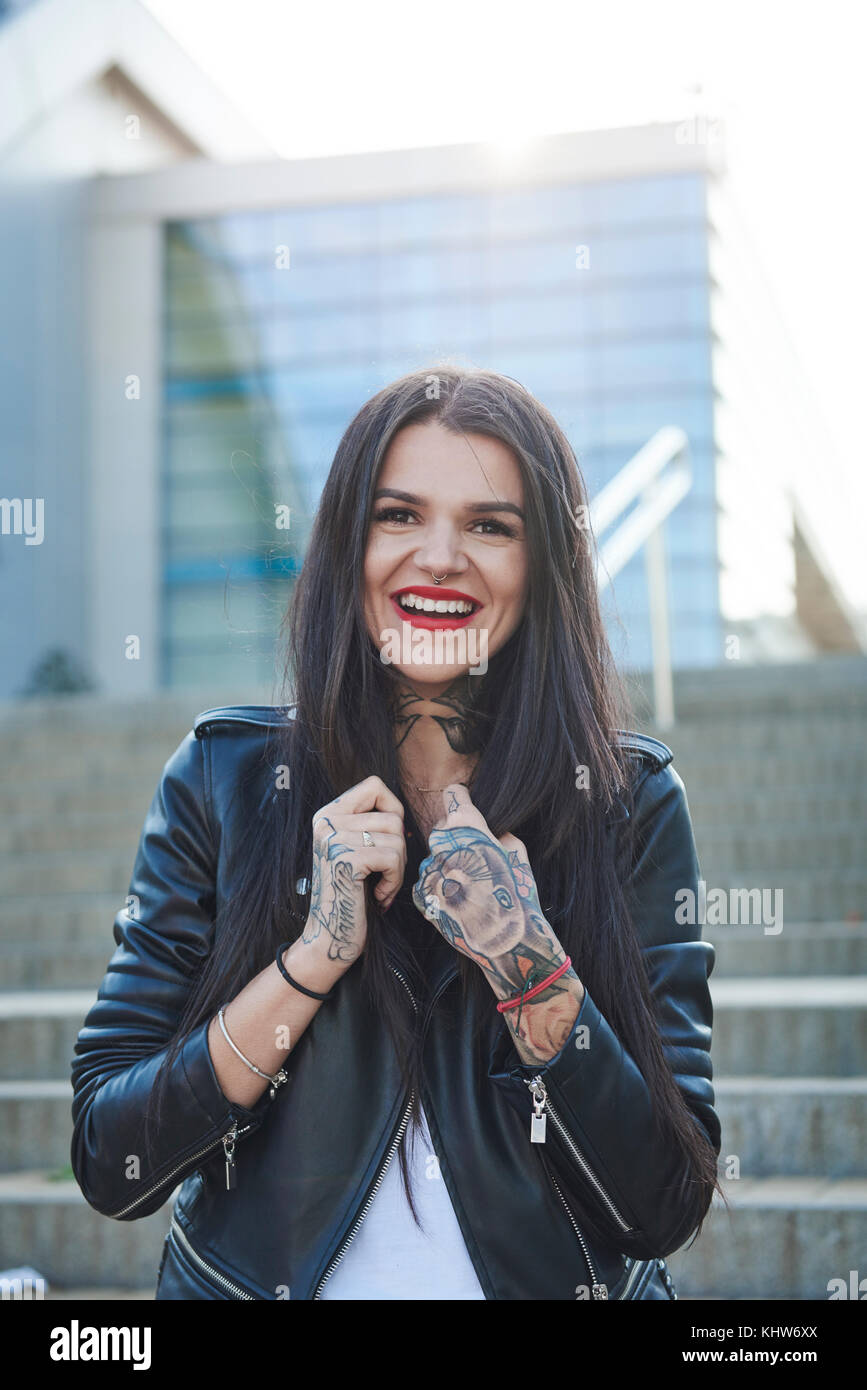 Portrait of young woman holding collars of jacket, smiling, tattoos on hands - Stock Image