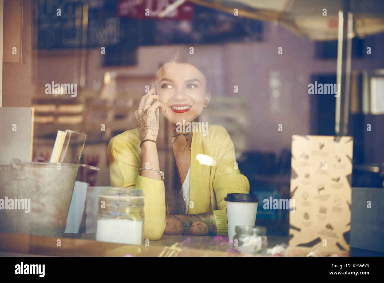 Young woman sitting in cafe, using smartphone, tattoos on hand, view through cafe window - Stock Image