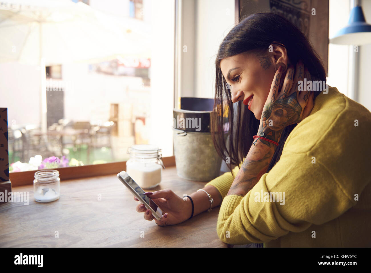 Young woman sitting in cafe, using smartphone, tattoos on arm and hand - Stock Image