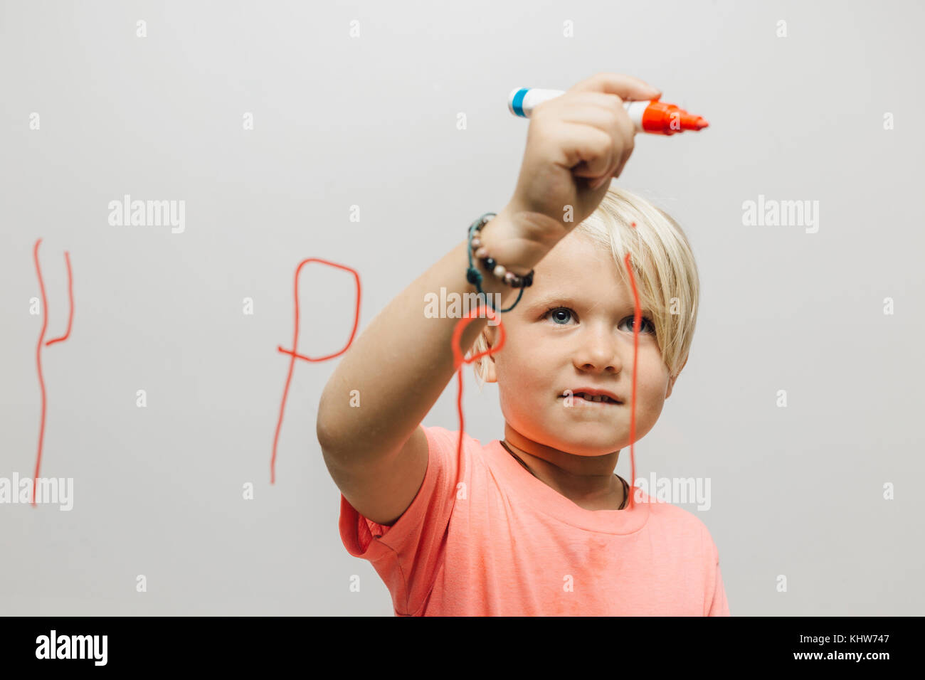Boy writing reversed letter P onto glass wall - Stock Image