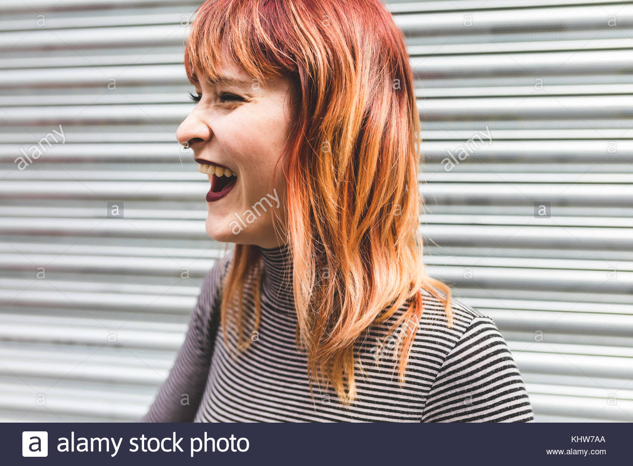 Portrait of a young woman with dyed hair, laughing - Stock Image