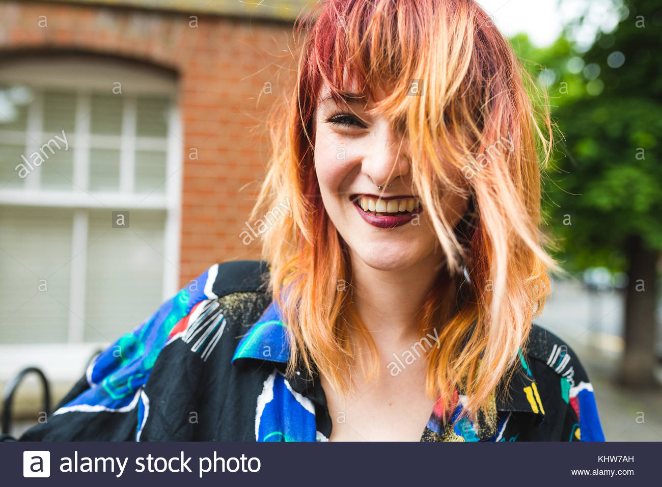 Portrait of young woman with dip dyed hair laughing - Stock Image