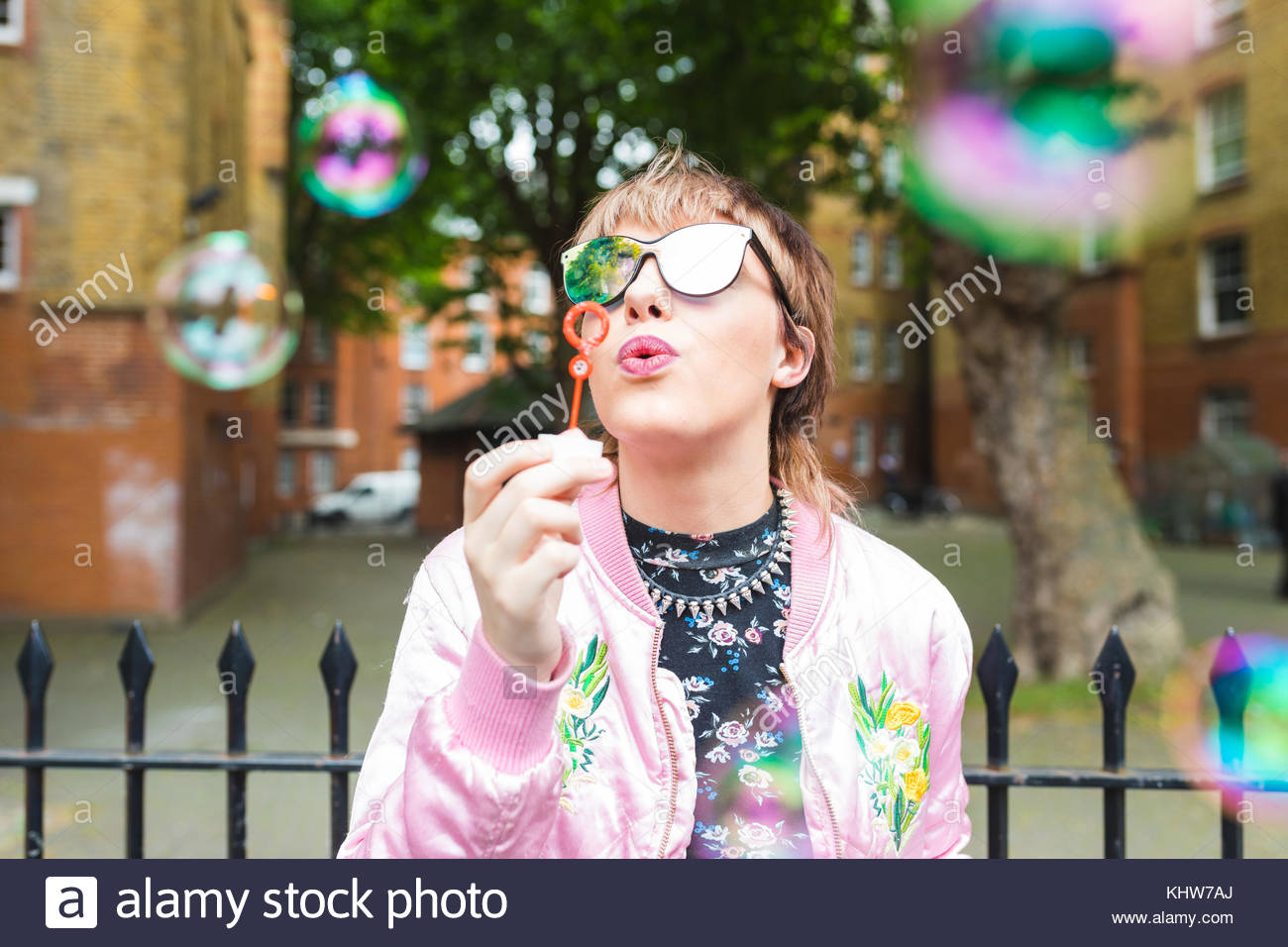 Retro styled young woman blowing bubbles - Stock Image