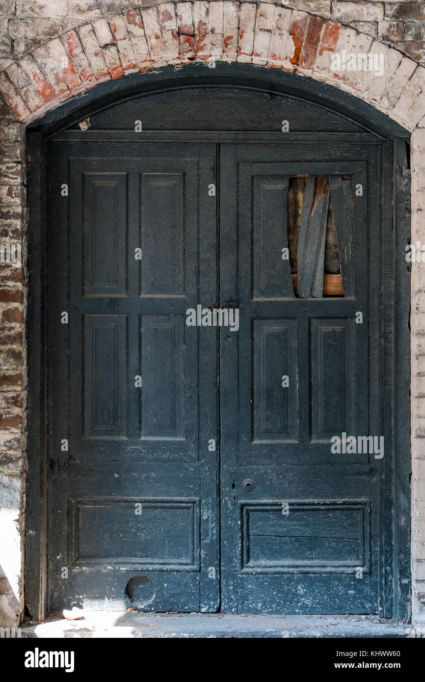 Old Damaged Wooden Doors with Brick Surround - Stock Image