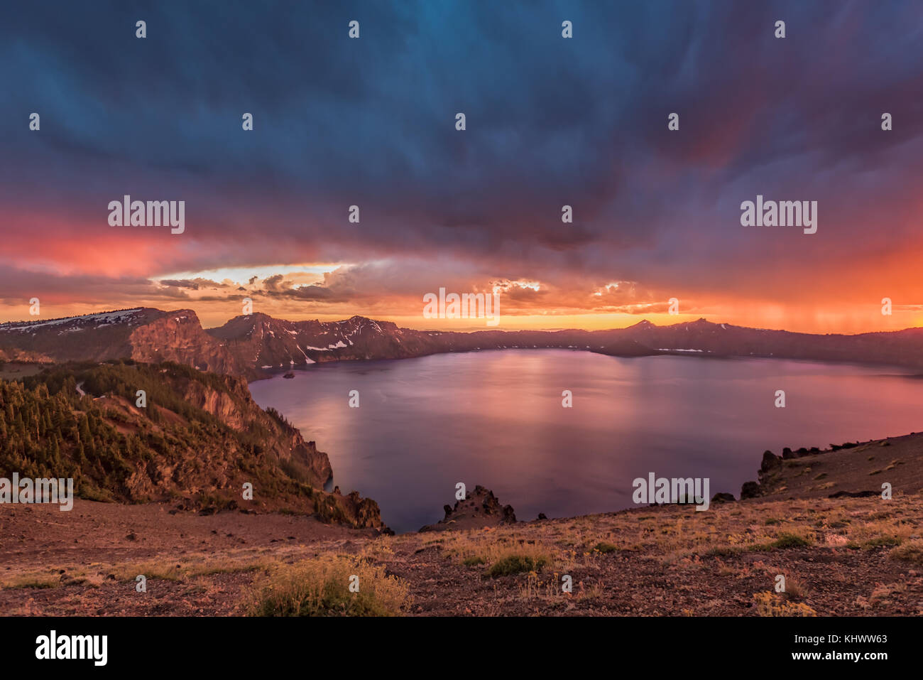 Orange Sunset and Storm Clouds Over Crater Lake in summer - Stock Image