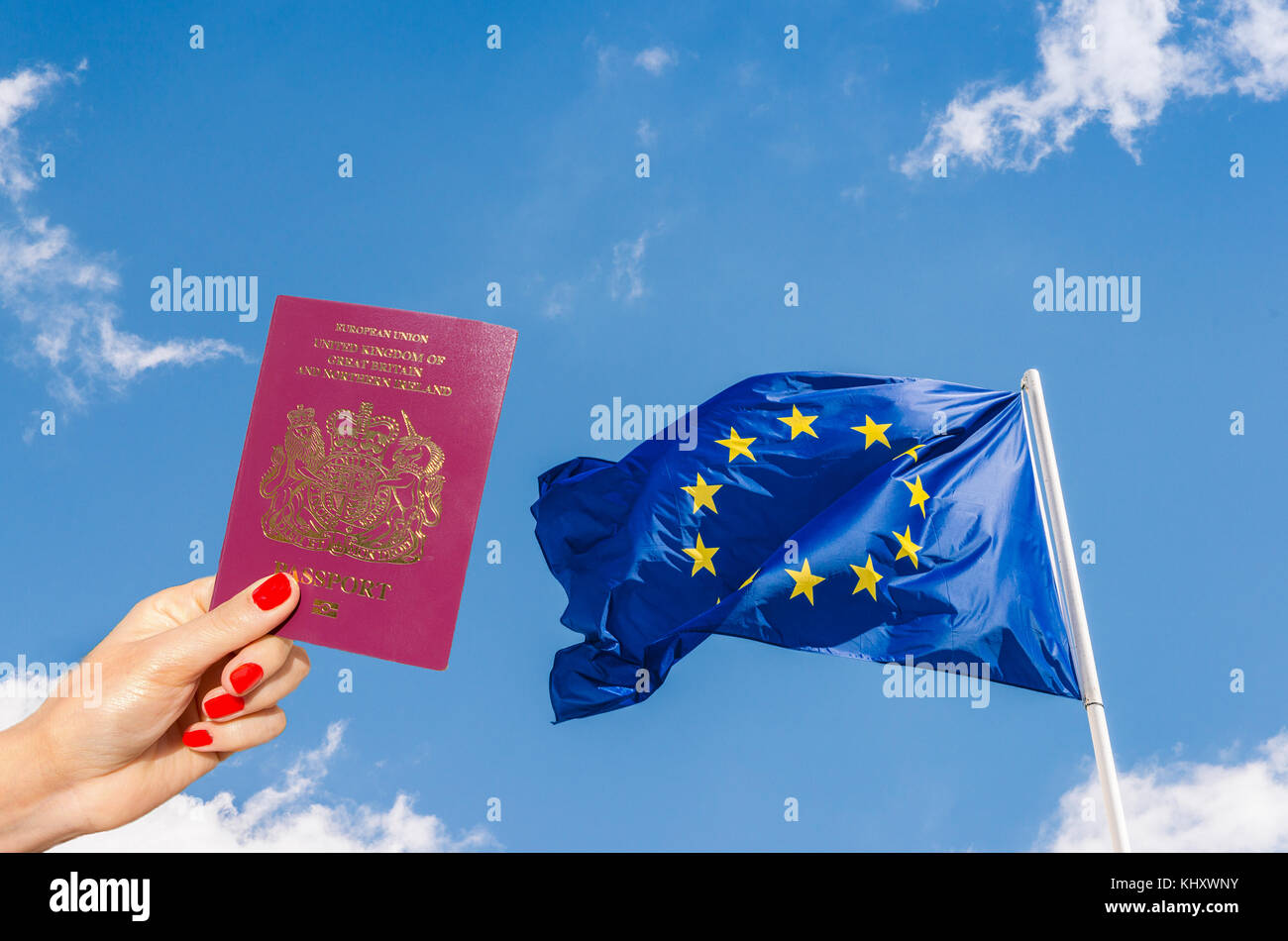 European Union (EU) flag against a blue sky with digital composite of woman holding a UK passport - UK is set to Stock Photo