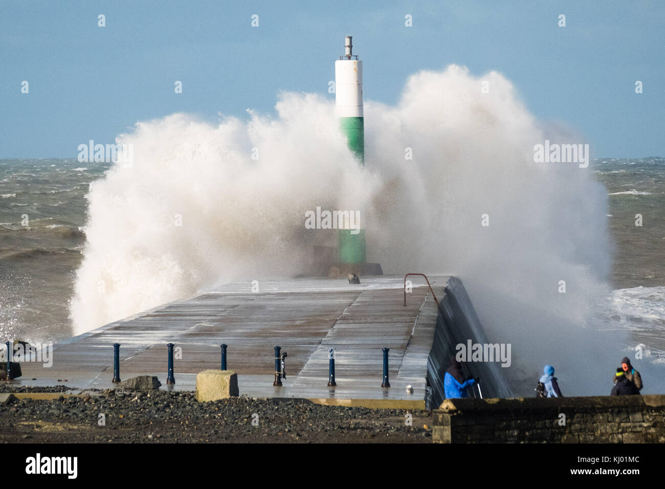 Aberystwyth Wales UK, Thursday 23 November 2017 UK Weather: A group of walkers look on as high tides and very strong - Stock Image