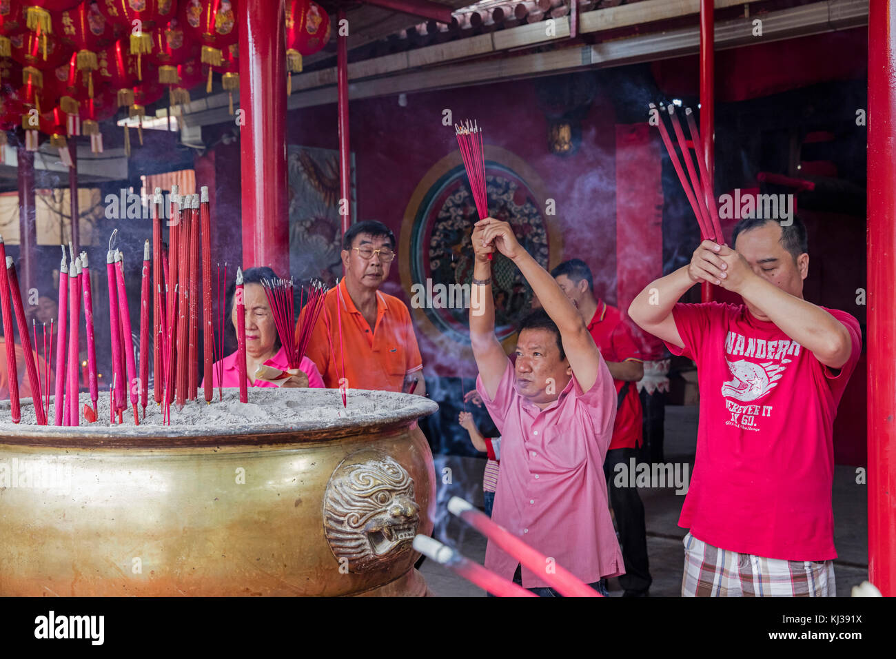 Chinese Indonesians worshipping by burning incense inside Chinese Buddhist temple at Jakarta, Indonesia - Stock Image