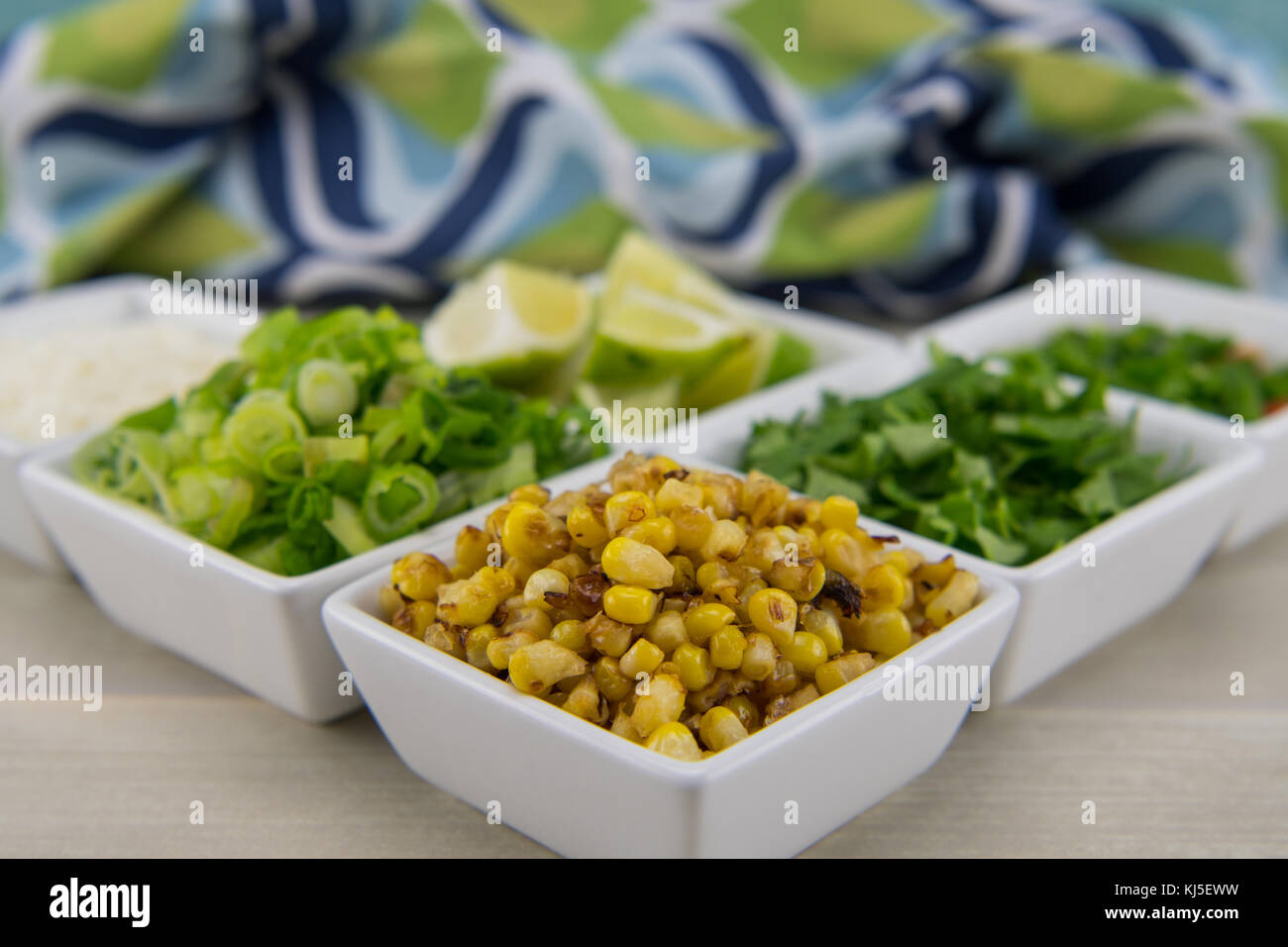 Roasted Corn in White Bowl in front of seasonings for street corn - Stock Image