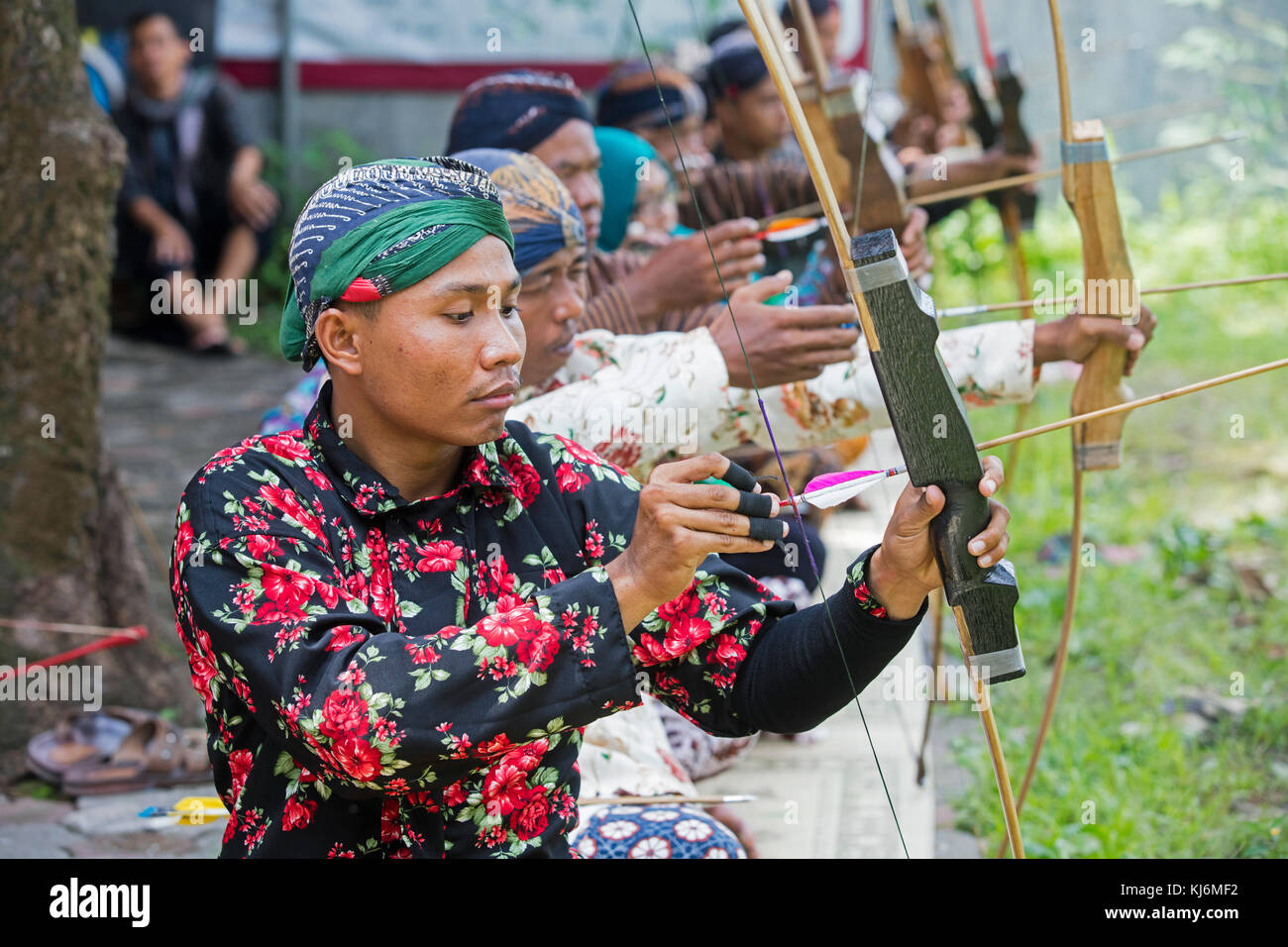 Indonesian men practicing Jemparingan / traditional Javanese archery by shooting bow and arrows in the city Yogyakarta, - Stock Image